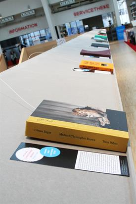 A wooden construction showing a line of books from the Aperture Award